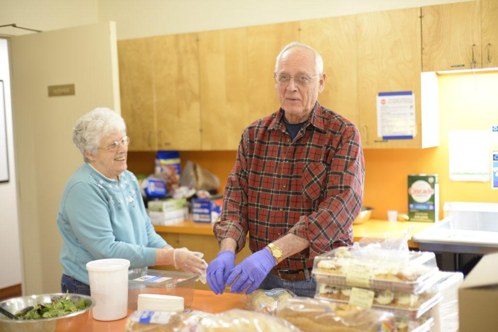 two volunteers preparing food